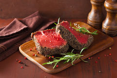 Raw beef steak with spices and rosemary on wooden background Stock Images