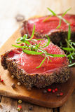 Raw beef steak with spices and rosemary on wooden background Royalty Free Stock Photography