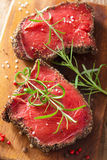 Raw beef steak with spices and rosemary on wooden background Royalty Free Stock Images