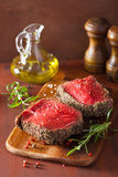 Raw beef steak with spices and rosemary on wooden background Royalty Free Stock Image