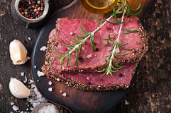 Raw beef steak with spices. And a sprig of rosemary Stock Image