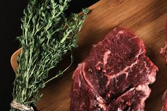 Raw beef steak with spices and thyme. On a black background Stock Photo