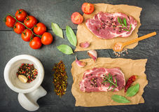 Raw beef steak with spices top view. Raw beef steak with spices, tomatoes on a dark table prepared for cooking top view Royalty Free Stock Image