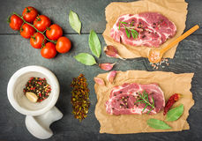 Raw beef steak with spices top view. Raw beef steak with spices, tomatoes on a dark table prepared for cooking top view Royalty Free Stock Photos