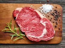 Raw beef steak. And spices on wooden cutting board, top view Royalty Free Stock Photo