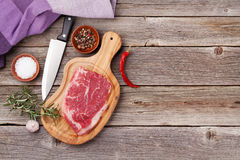 Raw beef steak and spices. On wooden table. Top view with copy space Royalty Free Stock Image