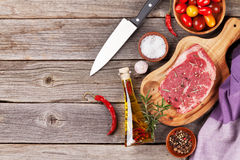 Raw beef steak and spices on wooden table. Top view vith copy space Stock Photos