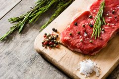 Raw beef steak with spicy ready to be cooked on wood. Raw beef steak with spicy ready to be cooked on wooden table. Copyspace Royalty Free Stock Photo