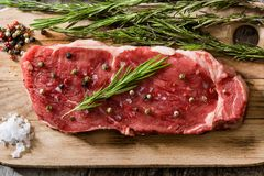 Raw beef steak with spicy ready to be cooked on wood. Raw beef steak with spicy ready to be cooked on wooden table. Top view Royalty Free Stock Photography