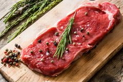 Raw beef steak with spicy ready to be cooked on wood. Raw beef steak with spicy ready to be cooked on wooden table. Close up Royalty Free Stock Photo