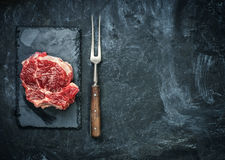 Raw beef steak on the stone plate over black table. Stock Photography