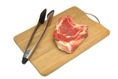 Raw Beef Steak,  Tongs On The Wood Cutting Board Isolated. Raw Beef Rib Eye Steak And  Tongs On The Bamboo Wood Cutting Board Isolated On White Background, Close Royalty Free Stock Image