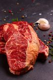 Raw beef steak. Two Raw beef steaks with spices on dark background close up Stock Photo