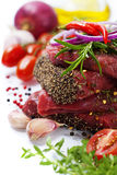 Raw beef steak. And vegetables over white Royalty Free Stock Photography