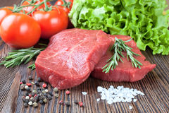 Raw beef steak with vegetables and spices. Raw beef steak  with vegetables and spices on brown wooden background Stock Images