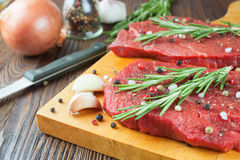 Raw beef steak with vegetables and spices. Raw beef steak  with vegetables and spices on brown wooden background Royalty Free Stock Photos