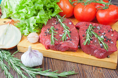 Raw beef steak with vegetables and spices. Raw beef steak  with vegetables and spices on brown wooden background Royalty Free Stock Image