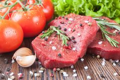 Raw beef steak with vegetables and spices. Raw beef steak  with vegetables and spices on brown wooden background Stock Photography