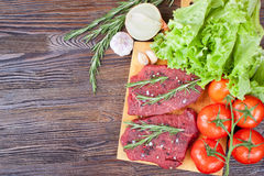 Raw beef steak with vegetables and spices. Raw beef steak on cutting board with vegetables and spices on brown wooden background Royalty Free Stock Image