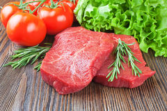 Raw beef steak with vegetables and spices. Raw beef steak on cutting board with vegetables and spices on brown wooden background Stock Photography