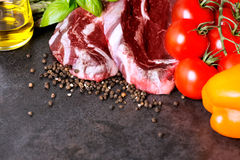 Raw beef steak and vegetables on table with copy space Stock Photos