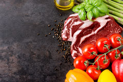 Raw beef steak and vegetables on table with copy space Royalty Free Stock Photography