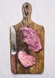 Raw beef steak on vintage cutting board with a knife for meat wooden rustic background top view close up royalty free stock photography