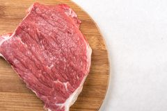 Raw beef steak on the wooden board with copy space above white marble.  Stock Image