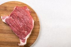 Raw beef steak on the wooden board with copy space above white marble.  Stock Photos