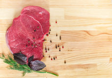 Raw beef steak on a wooden table. Royalty Free Stock Photo
