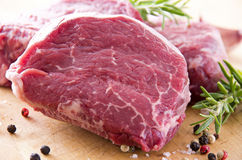 Raw Beef Steaks. As closeup on a wooden board Royalty Free Stock Images