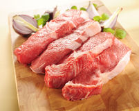 Raw beef steaks. Arrangement on a cutting board. Raw beef steaks on a cutting board and vegetables stock images
