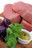 Raw Beef Steaks. Arrangement of Raw Beef Steaks with Green, Spices and Olive Oil closeup on Wooden Cutting Board Stock Photos