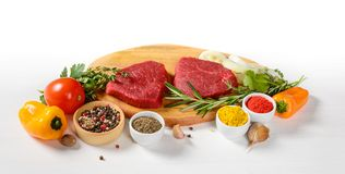 Raw beef steaks on a cutting board with spices. Herbs and vegetables on white wooden table background Stock Images