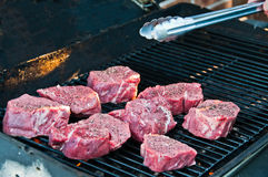 Raw Beef Steaks on the Grill. Eight butcher cut pieces of raw fillet mignon sit on a grill. Tongs are being held above the grill Royalty Free Stock Images