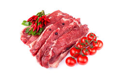 Raw Beef Steaks. With hot chilies, parsley, cherry tomatoes and juniper grains, on white background Stock Photography