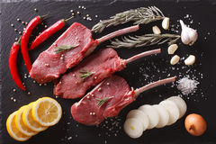 Raw beef steaks with ingredients on a slate closeup. Horizontal. Raw beef steaks with ingredients on a black stone table closeup. Horizontal top view Stock Images