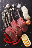 Raw beef steaks with ingredients on a slate closeup. vertical to. Raw beef steaks with ingredients on a black stone table closeup. vertical top view Royalty Free Stock Images