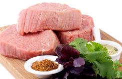Raw Beef Steaks. With Parsley and Basil, Spices and Olive Oil on Wooden Cutting Board  on white background Stock Image