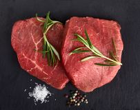 Raw beef steaks with rosemary. Fresh raw beef with rosemary on black background Stock Photo
