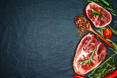 Raw beef steaks with spices and rosemary. Flat lay. Top view. Steak on the bonewith cherry tomatoes, hot pepper and herbs. Raw beef steaks with spices and Royalty Free Stock Image