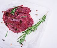 Raw beef steaks with spices and rosemary. On white paper, empty space on the right Stock Photos