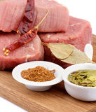 Raw Beef Steaks. With Various Spices and Olive Oil on Wooden Cutting Board closeup on white background Royalty Free Stock Photo