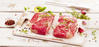 Raw Beef Steaks on  white wooden  cutting board. Stock Photo