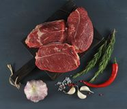 Raw beef steaks on wooden Board. Garlic, rosemary and spices on dark wooden background Royalty Free Stock Photo