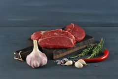 Raw beef steaks on wooden Board. Garlic, rosemary and spices on dark wooden background Royalty Free Stock Image