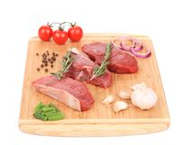 Raw beef steaks on a wooden cutting board. Isolated on a white background Stock Photography