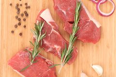 Raw beef steaks on a wooden cutting board. Located on the whole background Royalty Free Stock Photography