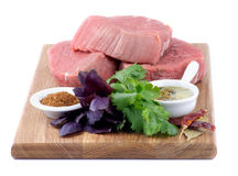 Raw Beef Steaks. Wooden Cutting Board with Three Raw Beef Steaks, Greens, Spices and Olive Oil isolated on white background Stock Photos
