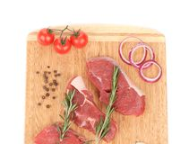 Raw beef steaks on a wooden cutting board. On a white background Royalty Free Stock Photo
